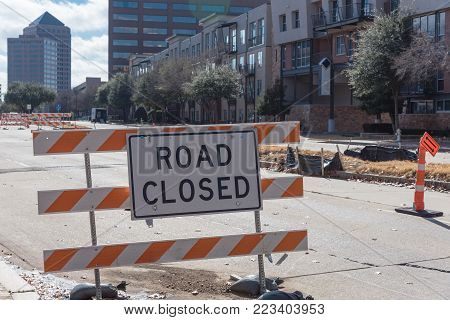 Close-up road closed sign in Downtown Irving, Texas, USA. Barricade closures, cones with urban buildings in background.