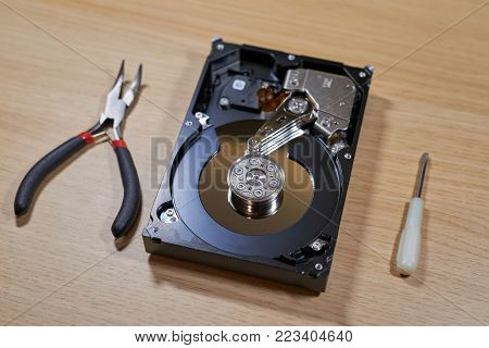 Disassembled hard disk drive lying on table with different repair tools