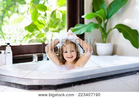 Little child taking bubble bath in beautiful bathroom with big garden view window. Kids hygiene. Shampoo, hair treatment and soap for children. Kid bathing in large tub. Baby boy with foam in hair.