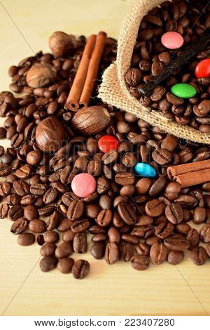 Coffee beans, multicoloured drops, cinnamon and vanilla. Ingredients for making a drink