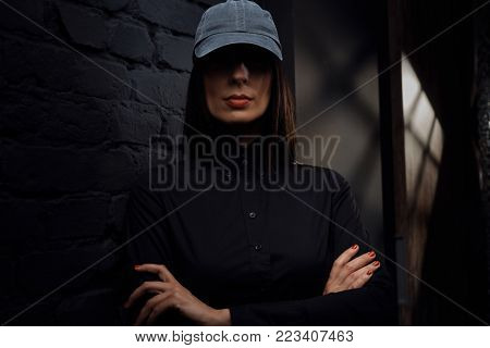Mysterious woman in black wearing black baseball cap, face covered by shadow. Unusual portrait photo in dark.