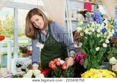 Young female florist working in flower shop. Portrait of beautiful caucasian girl self-employed in flower shop, smiling and looking at camera.