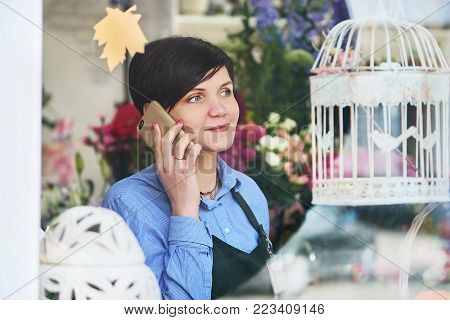 young female florist working in flower shop. polite girl communicates with customer on the phone. Business Flower Shop Owner. women calling on phone land line and looking outdoors through a window in the flower shop.