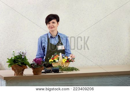 Smiling young female florist working in flower shop. Portrait of beautiful caucasian girl self-employed in flower shop, smiling and looking at camera. Place for text or ads