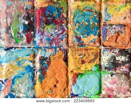 Artist and painting pallet, colour mixing oranges multicoloured