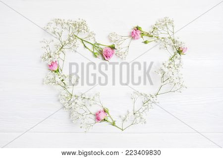 Mock up Composition heart of white flowers rustic style, for St. Valentine's Day with a place for your text. Flat lay, top view photo mock up.
