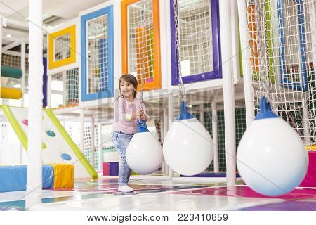Young girl playing with the giant hanging balls in a colorful playroom, having fun
