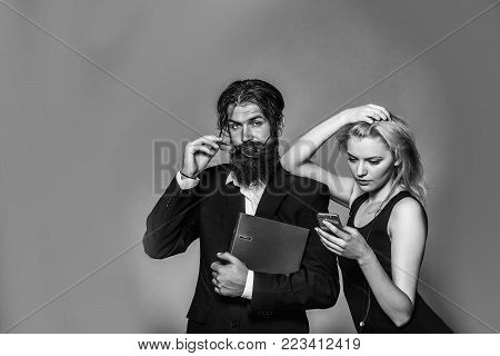 Serious couple of young blond woman in black dress with smartphone and handsome bearded hipster man rearranges glasses in suit with folder on grey wall