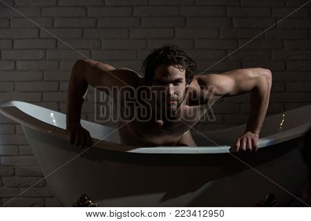 Man with muscular body in bath. Hygiene and healthcare. Bathroom and home comfort. Spa and relaxation, sexy man. Guy with wet hair sitting in bath tub.
