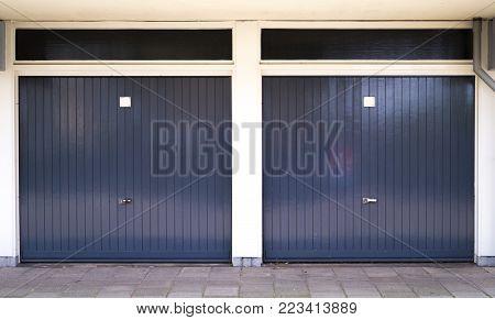two closed dark gray car garage doors with white pillars in between