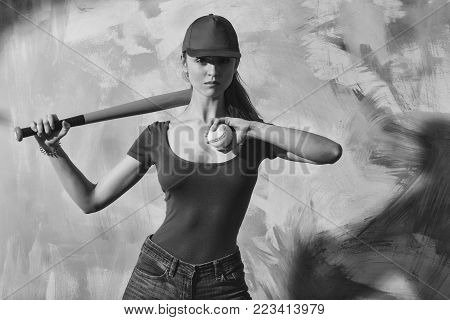 Pretty girl or sexy baseball player with blond hair in red cap, tshirt and blue jeans standing with green bat and ball on abstract yellow and pink wall
