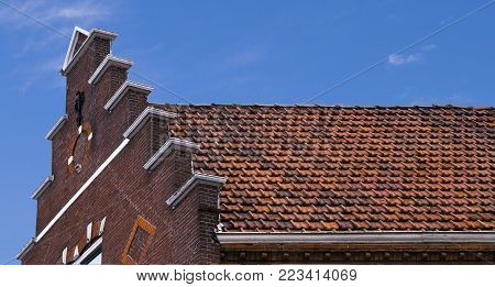 a traditional dutch stair rooftop house with orange rooftiles on a sunny blue sky day