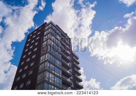 a high flat skyscraper apartment complex with white clouds in the background and a blue sky with sunshine