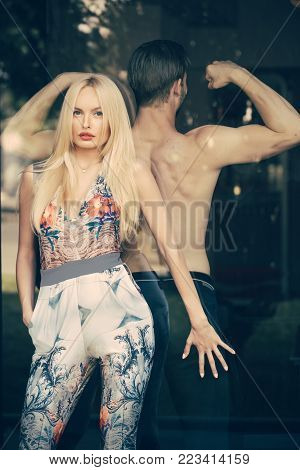 Girl and man with muscular torso indoor. Couple in love separated by glass window. Date, love, relations. Barrier in communication. Divorce, break up concept.