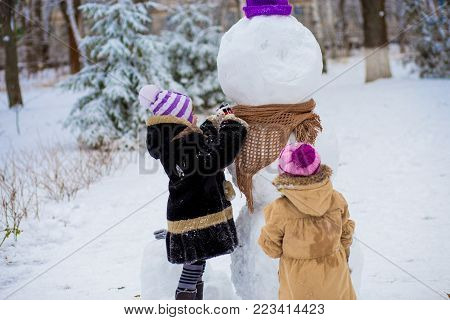 A small cheerful girls put on a scarf for a big snowman. A cute little sisters has fun in winter park, wintertime