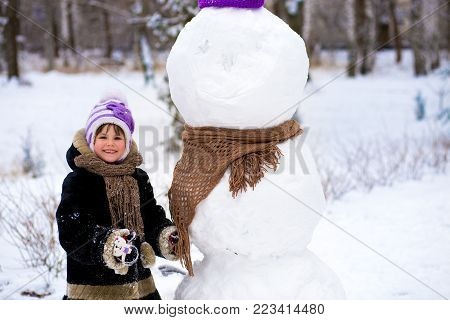 A small cheerful girl puts on a scarf for a big snowman. A cute little girl has fun in winter park, wintertime