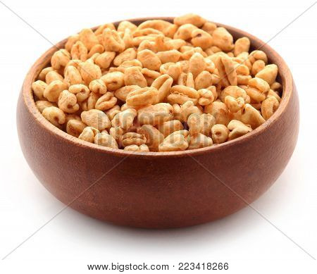 Golden Puffed Wheat In Bowl Over White Background