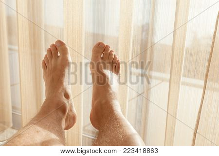 Relaxed male feet lay in sunlight near wide window with tulle