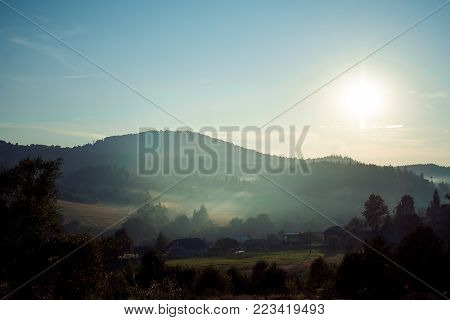Panorama view of the beautiful green mountains covered with rustic houses during the sunset. View of the sunlits