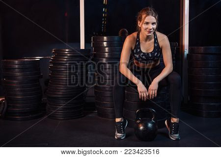 Woman working out with kettle ball at gym. Woman resting between approaches