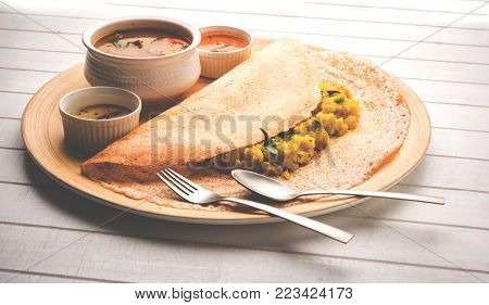 Masala dosa with chutney and sambar and potato sabzi. Cone, triangle or roll shape, selective focus