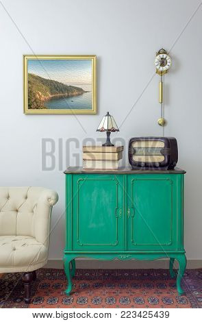 Interior shot of green vintage sideboard with old radio, stack of old books, and table lamp on background of off white wall with hanged painting, orange ornate carpet, and cream armchair