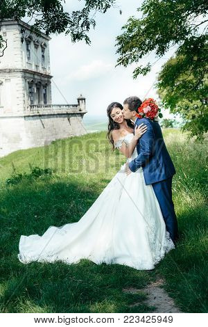 Full-length romantic wedding shot of the handsome groom kissing the gogeous smiling bride in cheek in the park