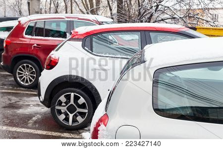 Picture of cars at a parking space & blue parking sign in the city on a winter day