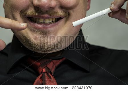 A cigarette is in the man's hand. A cigarette is not lit. A man points to the cigarette with his finger. Yellow teeth. No smoking.