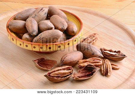 Pecan nuts in ceramic bowl on a wooden background