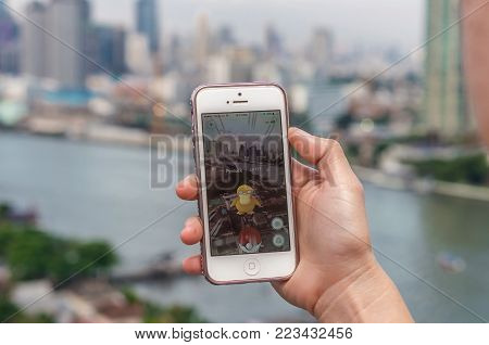 Bangkok, Thailand - Aug 6, 2016 : Hand holding Apple iPhone5 mobile phone showing the Pokemon Go application at screen over the bangkok cityscape photo blurred background on August 6, 2016, thailand