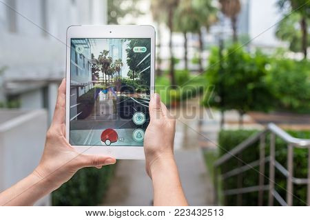 Bangkok, Thailand - Aug 7, 2016 : Hand holding Apple ipad mini2 tablet showing the Pokemon Go application at screen over the walk way with park photo blurred background on August 7, 2016, thailand