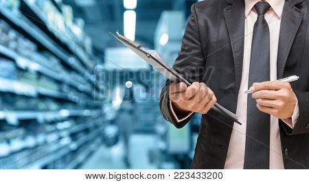 Businessman writing the file pad on Abstract blurred photo of store in department store bokeh background, business shopping concept