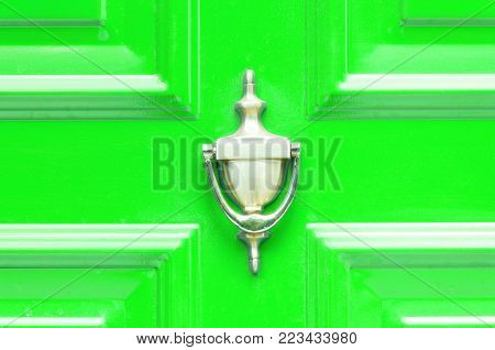 Door knocker. Old antique golden brass knocker on the abstract green wooden doors for knocking close up