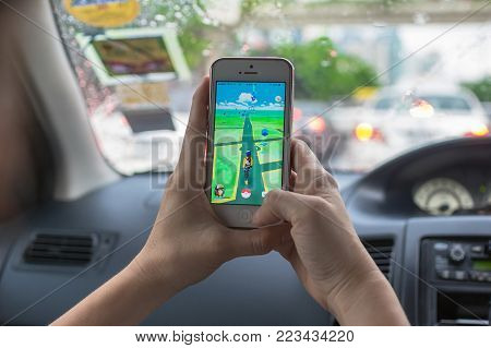 Bangkok, Thailand - Aug 7, 2016 : Hand holding Apple iPhone5 mobile phone showing the Pokemon Go application at screen in the car over on the way photo blurred background on August 7, 2016, thailand