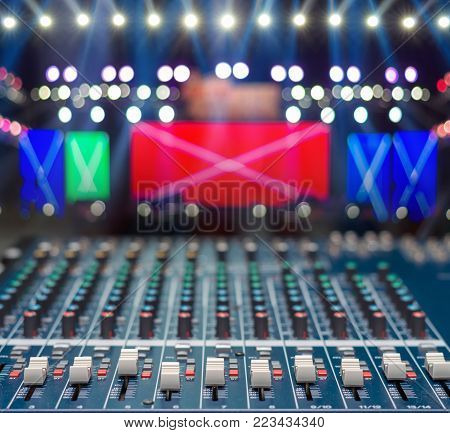 audio mixer over the Stage Spotlight with blue luminous rays and Blurred Photo bokeh from light,musical concert and instrument concept