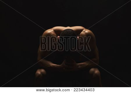 Pensive strong man sitting with head down. Male fitness model with naked torso showing strong neck and biceps muscles. Studio shot on black background, low kye, copy space