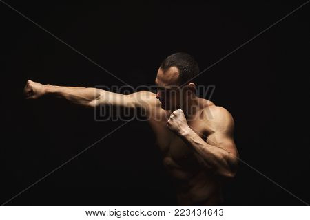 Athletic man make punch. Handsome fitness model show naked torso, muscular body. Strong hands, shoulder muscles and biceps. Studio shot on black background, low key. Kickboxing and fight sport concept