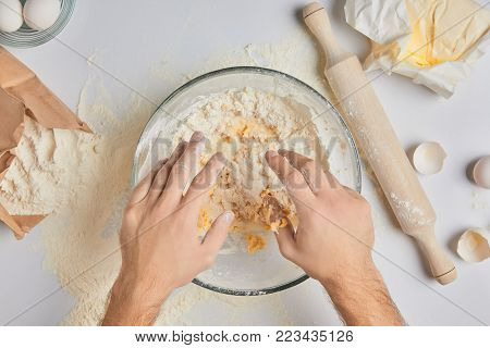 cropped image of chef kneading dough in bowl