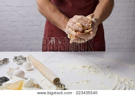 cropped image of chef kneading dough in hands