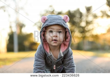Baby in a super cute mouse, animal costume, happy one year old girl. Baby loves outdoors and parks