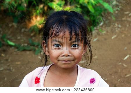 LUANGPRABANG, LAOS - JANUARY 21, 2018: Unidentified smiling little Lao girl on the street of a city.