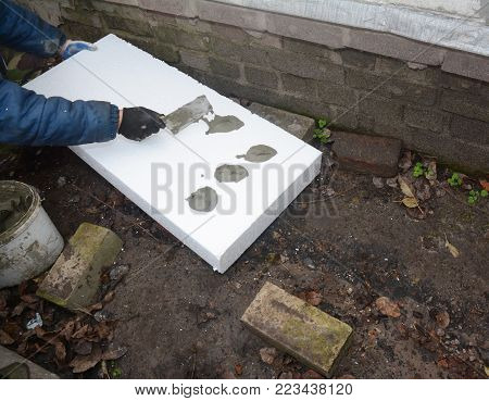 Contractor Insulating House Foundation with styrofoam insulation sheets. Wall insulation with foam board. Rigid Foam Insulation.