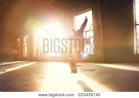 A young skater in a white hat and a black sweatshirt does a trick with a skate jump in an abandoned building in the backlight of the setting sun. The concept of youth underground culture and skateboarding