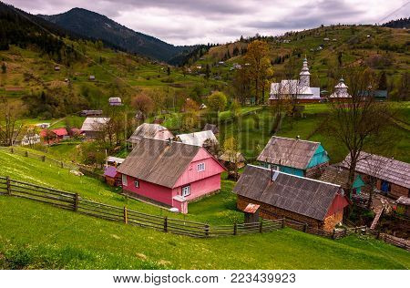 Synevyrs'ka Poliana village in Carpathians. lovely rural landscape with wooden fences on grassy slopes and a church on hillside among houses. beautiful nature springtime scenery in mountains