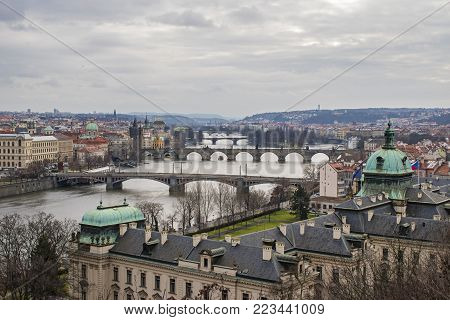 Panorama of the old part of Prague from the Letna park. Beautiful view on the bridges over the river Vltava at cloudy winter day. View on Straka Academy from Hanau pavilion. Czech Republic.