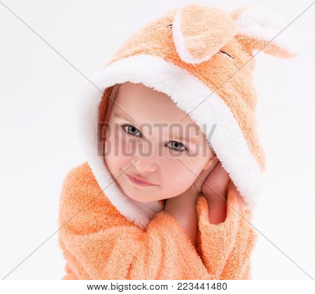Shy little bunny girl in a peachy robe, smiling and touching her face
