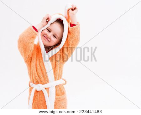 Lovely kid playing in a bathrobe with bunny ears, pretending she is a rabbit