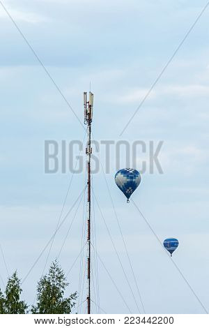 Minsk, Belarus - 10 September 2017: Two balloons, flying around the mast with receiving and transmitting equipment