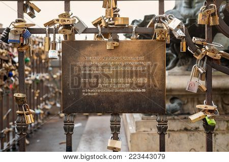Florence, Italy - December 22, 2017: Many love padlocks locked on rusty railing at Old Bridge, in Florence, despite the ban posted.